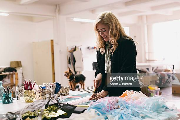 Female textile designer cutting textiles in design studio
