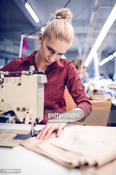 Female Textile Factory Worker Sewing Materials On Machine