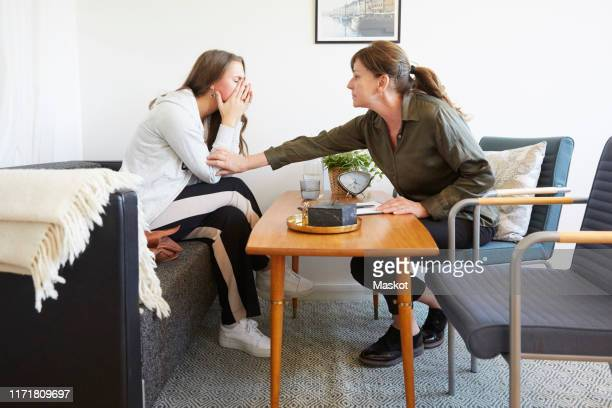 female therapist consoling teenage patient during session at workshop - psychiatrist's couch stock pictures, royalty-free photos & images