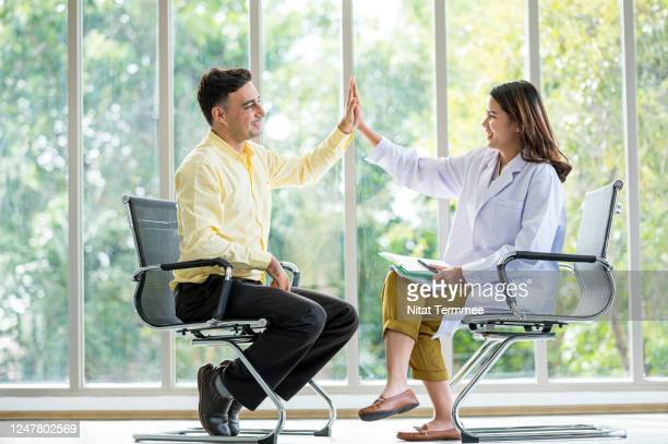 female therapist gives mature male client a high five in the counseling session. successful, hopeful expression, mental health and counseling concept. - bewustwording over geestelijke gezondheid stockfoto's en -beelden