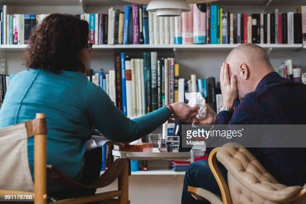 female therapist giving tissue to crying patient at home office - psychiatrist's couch stock pictures, royalty-free photos & images