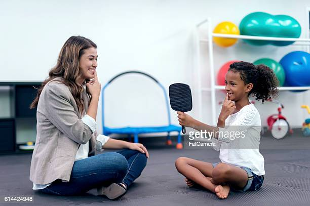 Female therapist helping a young African American girl in therapy