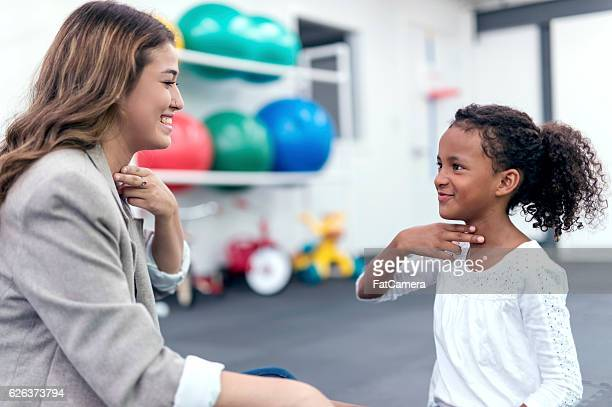 Female therapist helping African American girl in speech therapy exercise