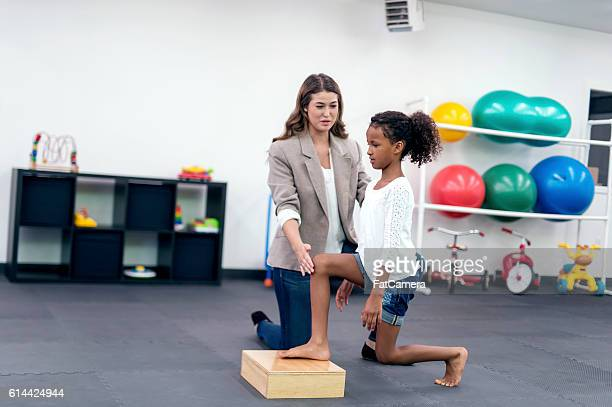 Female therapist helping young African American girl in therapy