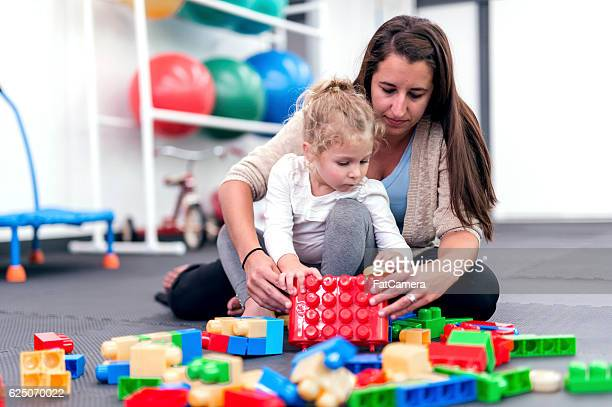 Female therapist helps young girl with a building exercise