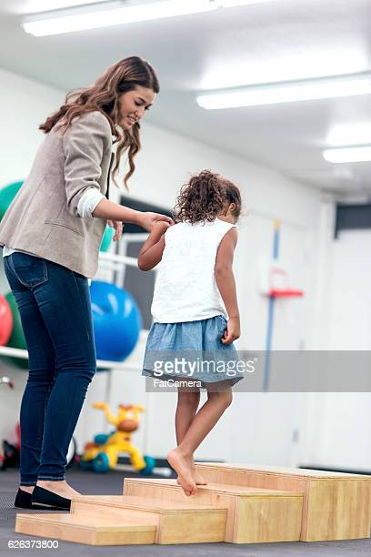 Female therapist holding ethnic girls hand walking up stairs