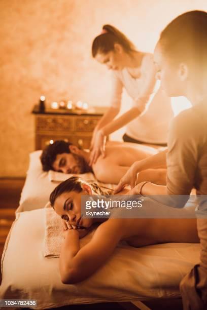 femininos terapeutas massagem jovem casal no spa. - health farm - fotografias e filmes do acervo