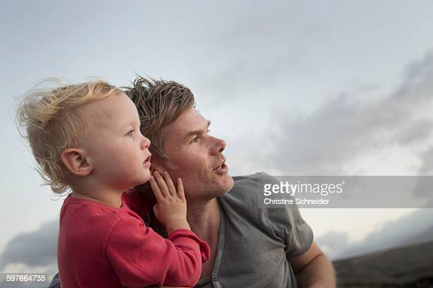 female toddler and father looking up and watching - leanintogether stock pictures, royalty-free photos & images