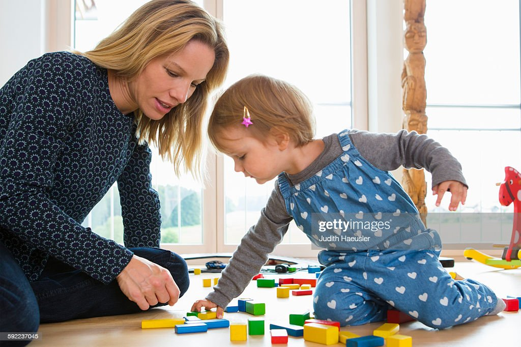 Female toddler and mother playing with building bricks on living room floor : Stock Photo