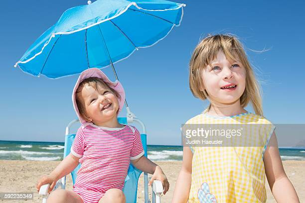 Female toddler and sister looking up from beach