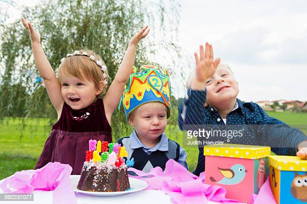 female toddler and two young brothers at birthday party in garden - happybirthdaycrown stock pictures, royalty-free photos & images
