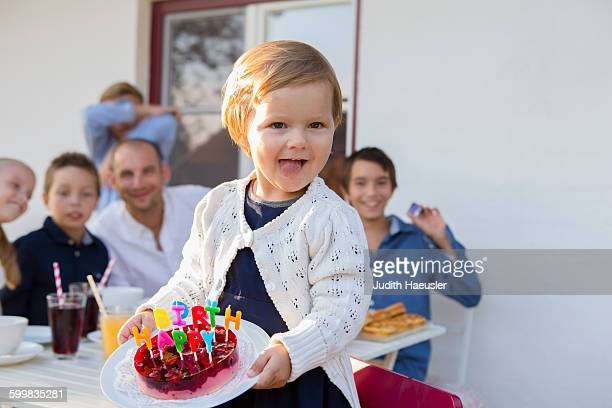 Female toddler carrying birthday cake on patio