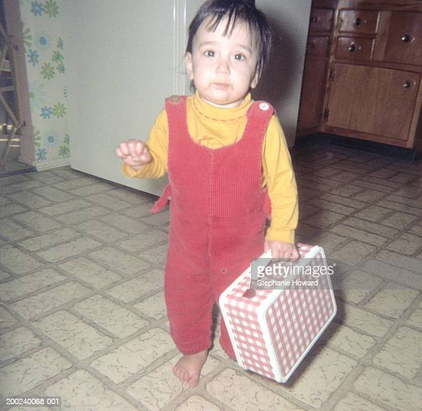 Female toddler (15-18 months) carrying lunch pale, portrait