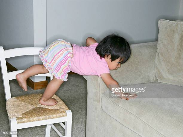 female toddler climbing from chair to couch - bent over babes stock pictures, royalty-free photos & images
