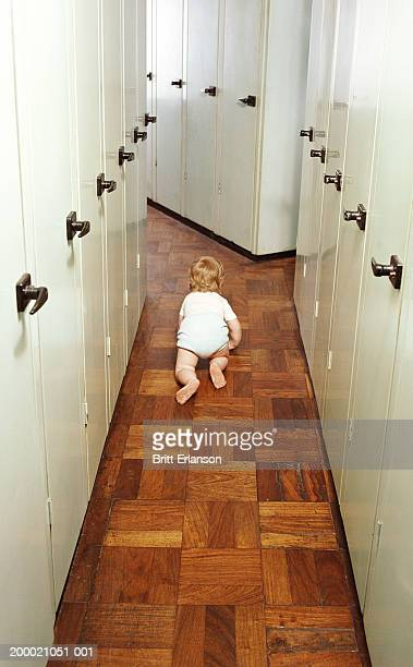 Female toddler (18-21 months) crawling along corridor, rear view