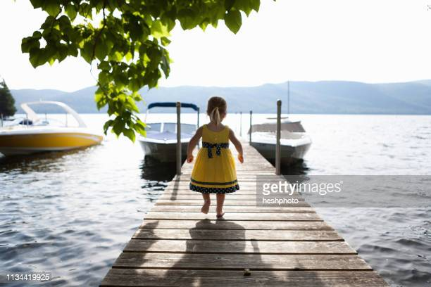 female toddler exploring pier, silver bay, new york, usa - heshphoto stock pictures, royalty-free photos & images