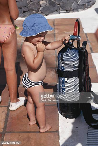 female toddler holding aqualung pipe by swimming pool - aqualung diving equipment stockfoto's en -beelden