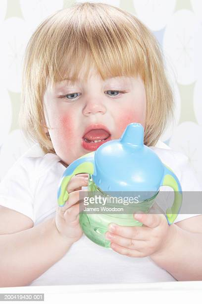 Female toddler (12-15 months) holding bottle, close-up