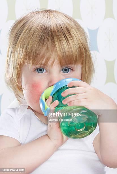 Female toddler (12-15 months) holding bottle, drinking, portrait,