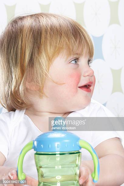 Female toddler (12-15 months) holding bottle, side view, close-up