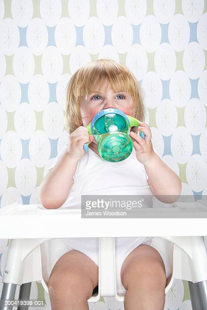 Female toddler (12-15 months) in high chair, drinking from bottle,