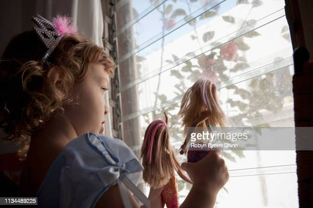 female toddler looking out of window holding up dolls - 人形 ストックフォトと画像