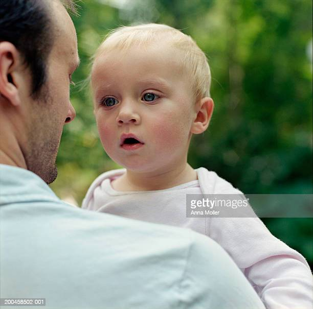 Female toddler (15-18 months) looking over father's shoulder