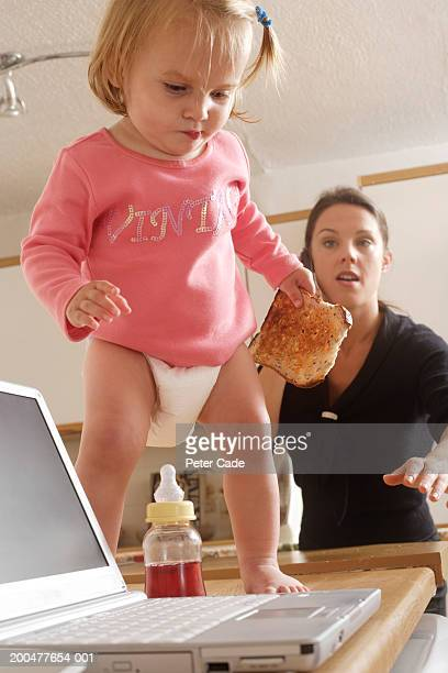 Female toddler (18-21 months) on table by laptop, mother in background