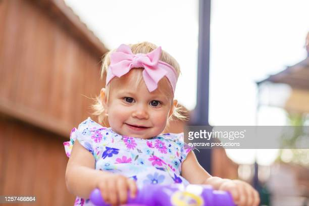 female toddler outdoors on patio riding a push toy tricycle - eyecrave  stock pictures, royalty-free photos & images