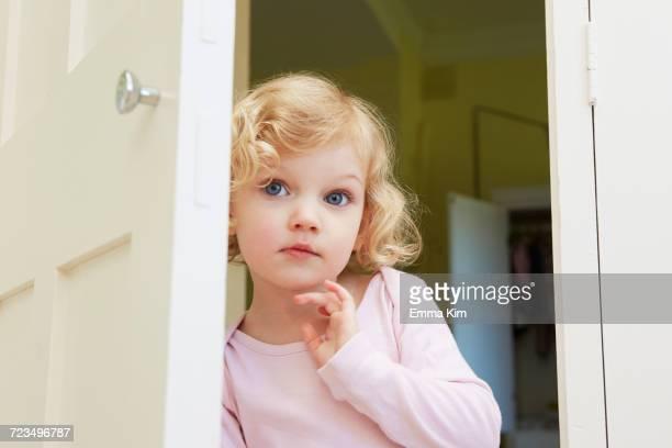 Female toddler peering from door