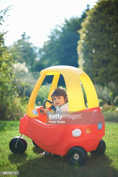 Female toddler playing in toy car in the garden