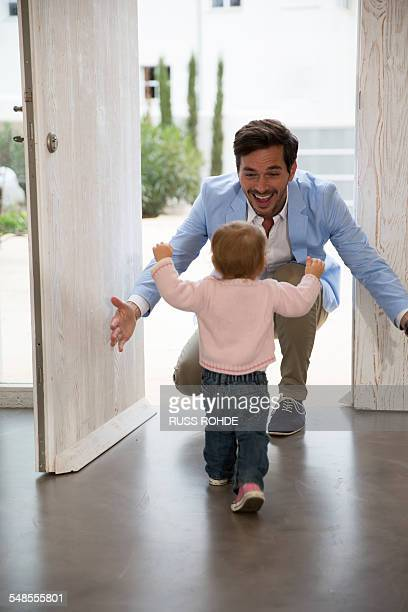 Female toddler running to fathers arms at front door