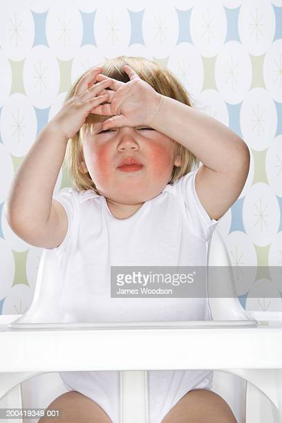 Female toddler (12-15 months) sitting in high chair, hands on forehead