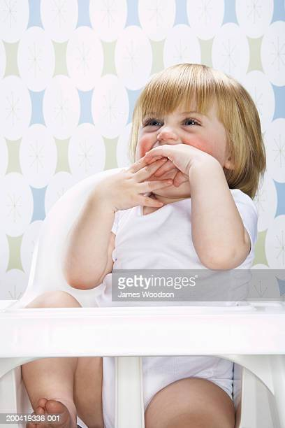 Female toddler (12-15 months) sitting in high chair, hands on mouth,