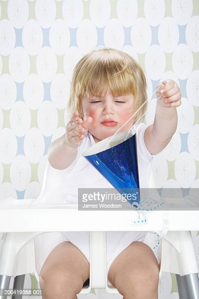 Female toddler (12-15 months) sitting in high chair, holding party hat