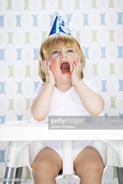 Female toddler (12-15 months) sitting in high chair, yawning, close-up