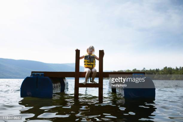 female toddler sitting on floating platform, silver bay, new york, usa - heshphoto stock pictures, royalty-free photos & images