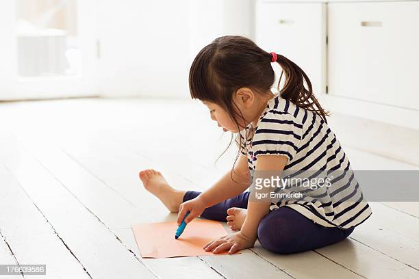 Female toddler sitting on floor drawing