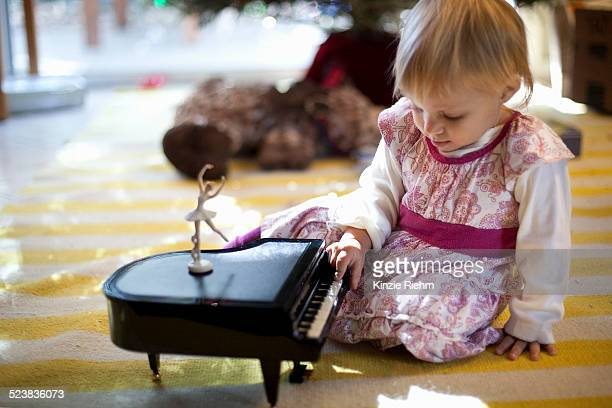 Female toddler sitting on living room floor playing with toy piano music box at Xmas