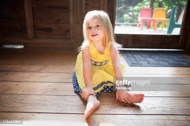 female toddler sitting on wooden floor - heshphoto stock pictures, royalty-free photos & images
