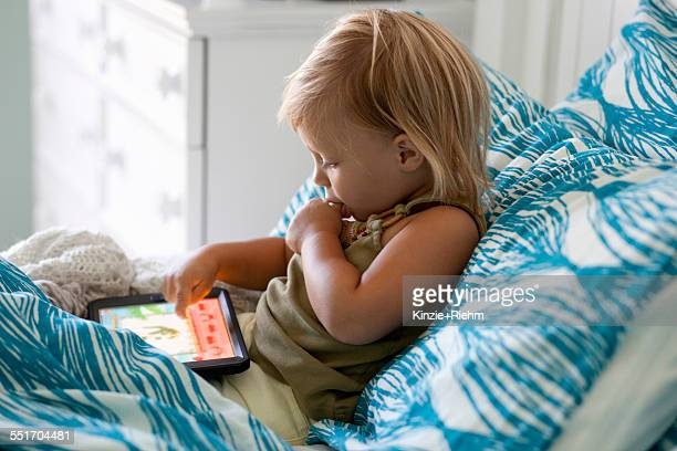Female toddler sitting up in bed using digital tablet