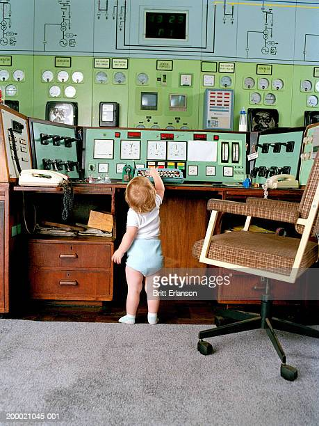 Female toddler (18-21 months) touching control panel, rear view