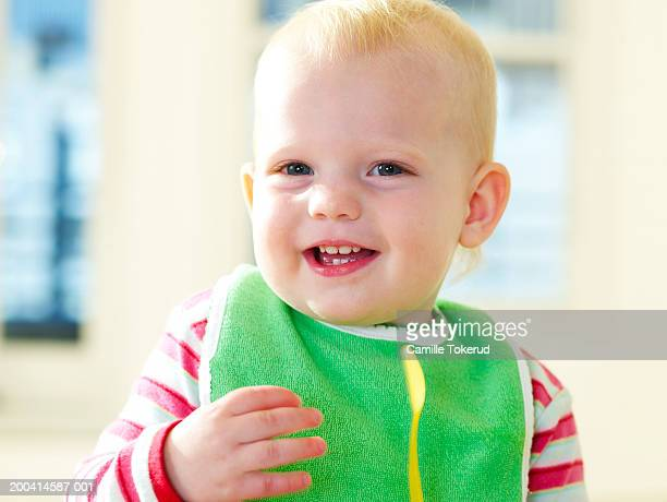 Female toddler (15-18 months) wearing bib, smiling