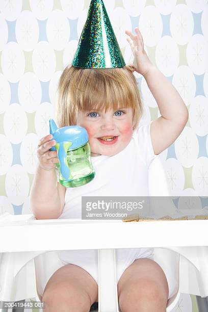 Female toddler (12-15 months) wearing party hat, holding bottle,