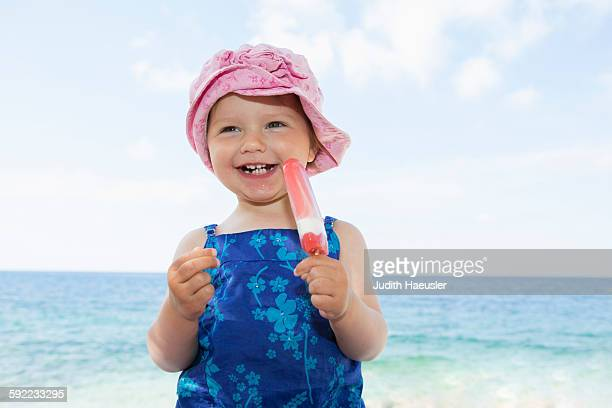 Female toddler wearing sunhat eating ice lolly on beach