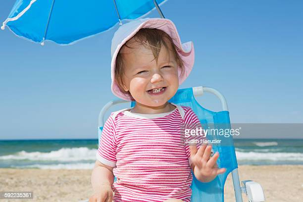 Female toddler wearing sunhat on beach chair