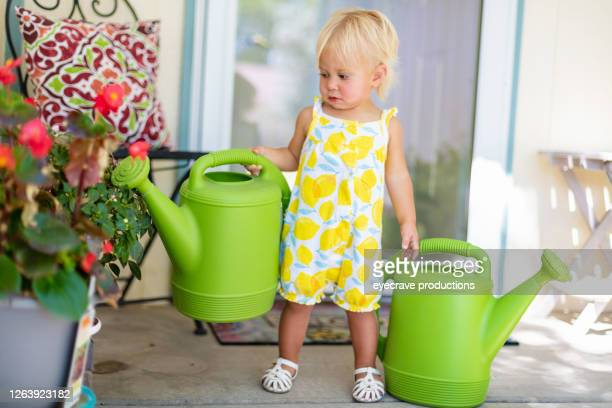 female toddler with blond hair water flowers on front porch - eyecrave  stock pictures, royalty-free photos & images
