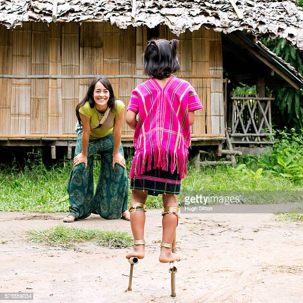 female tourist and local child (4-5) in village, chiang mai, thailand - hugh sitton stock pictures, royalty-free photos & images