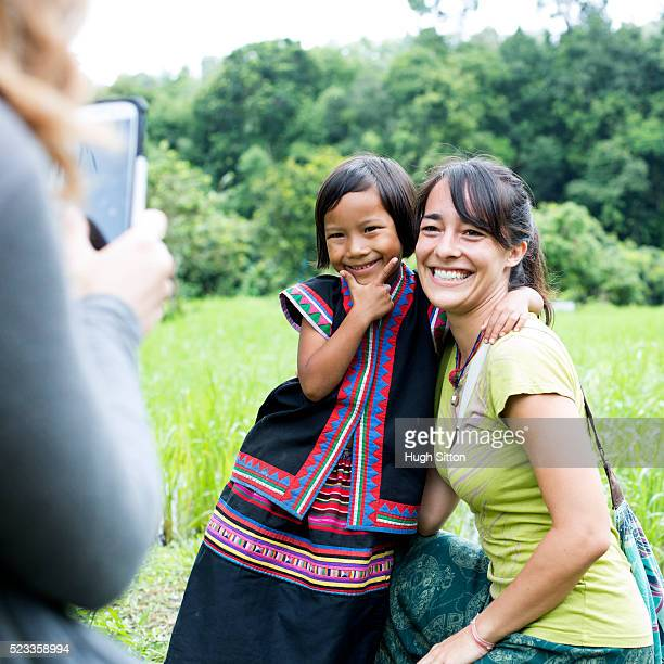 female tourist and local child (4-5) posing for photo, chiang mai, thailand - hugh sitton stockfoto's en -beelden