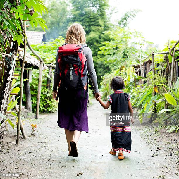 female tourist and local child (4-5) walking through village, chiang mai, thailand - hugh sitton stock-fotos und bilder